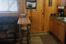Cozy eating area for two, plus two TV trays next to stove.
