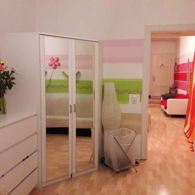 Schlafzimmer mit Blick in den Flur. Ein sehr geräumiger Kleiderschrank + Kommode stehen euch zur Verfügung.
