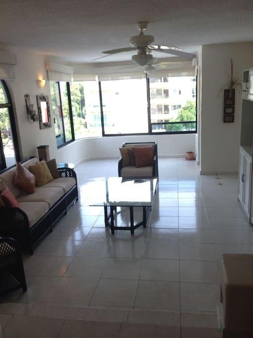Sala amplia con 2 sillones, sofá, mesa central, 2 muebles laterales de madera, amplias ventanas al exterior.