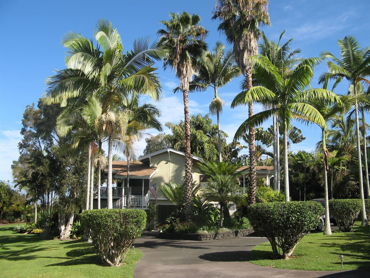 This 5 bedroom cedar mansion has 5 bedrooms, 5 bathrooms and 3 lanais.   This photo shows the circular driveway entrance from the parking area and begins the two acres of lush tropical gardens and well manicured lawn.