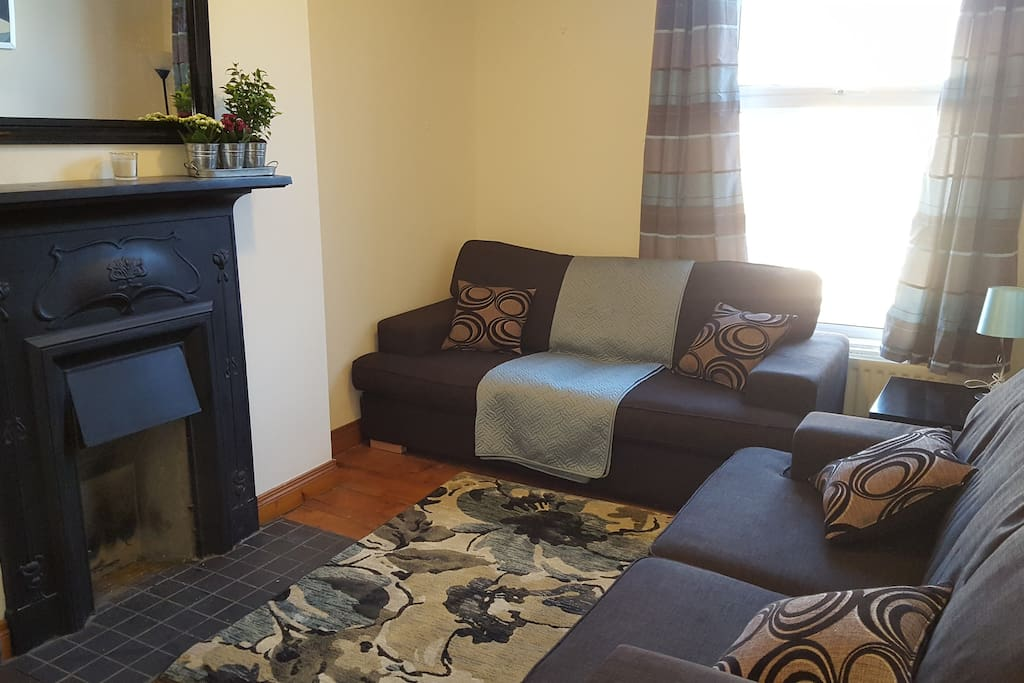 Living room with original fireplace and wooden flooring Sofa converts to a double bed