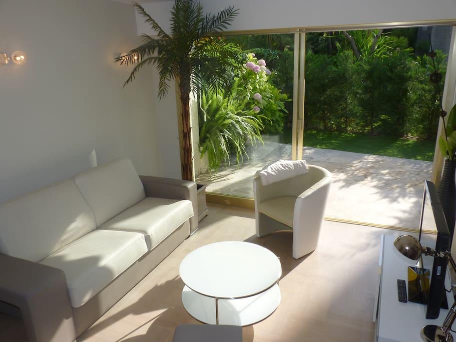 Salon ouvert sur la terrasse et le jardinet privé avec lits de soleil, sans vis-à-vis