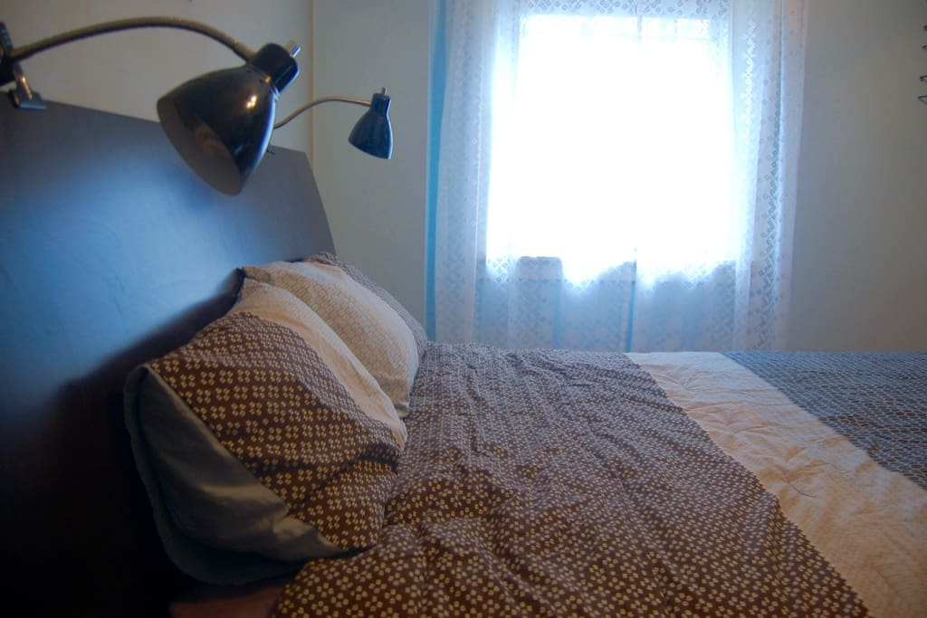 The blue and grey bedroom also features... reading lights.