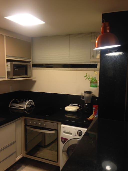 Cozinha - forno e fogão elétricos, máquina de lavar e seca.