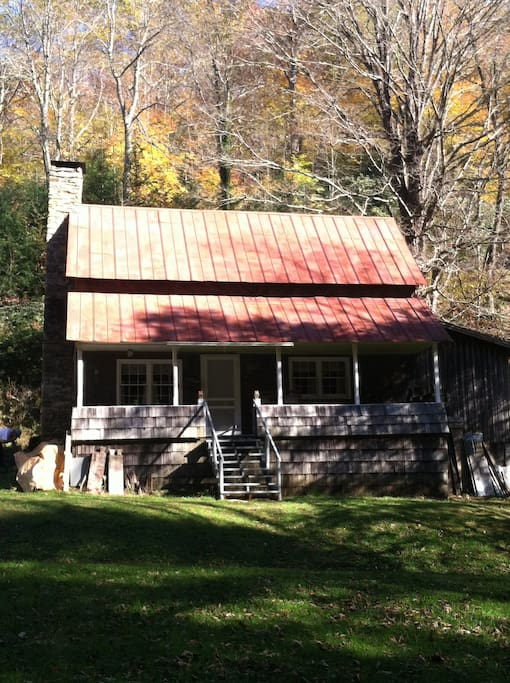 Front view of Cabin with wide front porch complete with rockers and a swing