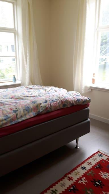 Stort dobbeltrom med dør inn til mindre rom med enkeltseng