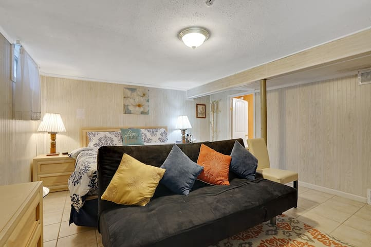 Huge size basement bedroom with king sized bed, private full bat, 2 night stands, 2 table lamps, new cute  comforter, additional comfy thin quilt, new big LED Samsung TV, kids books and several toys, chest, dresser with mirrors, chair, rug and futon