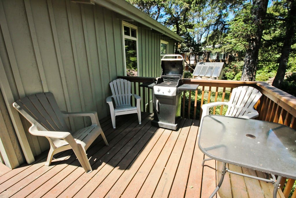"""L"" shaped upper deck with a gas BBQ, patio table and chairs."