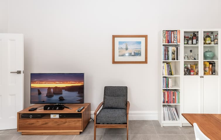 Apple TV with small library and reading chair