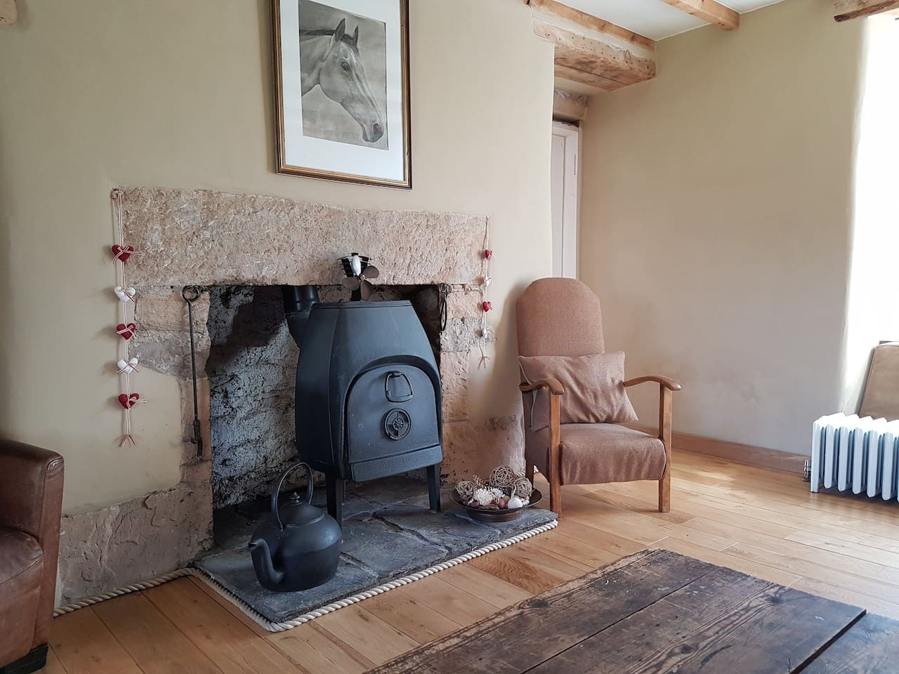 9ft high ceilings. Cosy but large, modern country style living room, with  wood burner that can be used as an open fire. Polished oak floor and ample seating.
