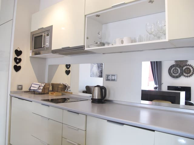 Full kitchen with fridge, microwave, washing machine, coffee maker, full set of utensils and cookware.