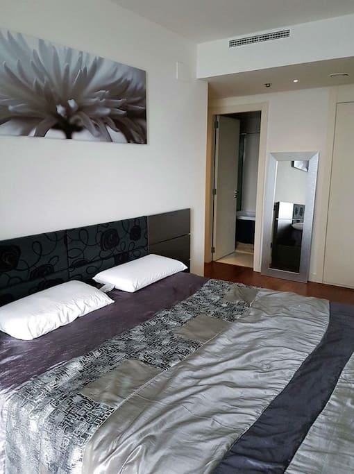 Bedroom with huge bed and private shower