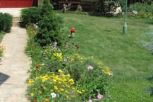 Large grean yard with flowerbeds for rest and fun outside the house