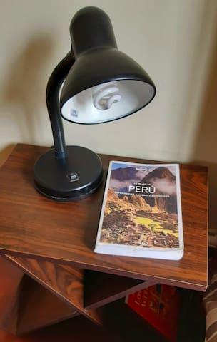 Mesita de noche con lampara de lectura e información turistica