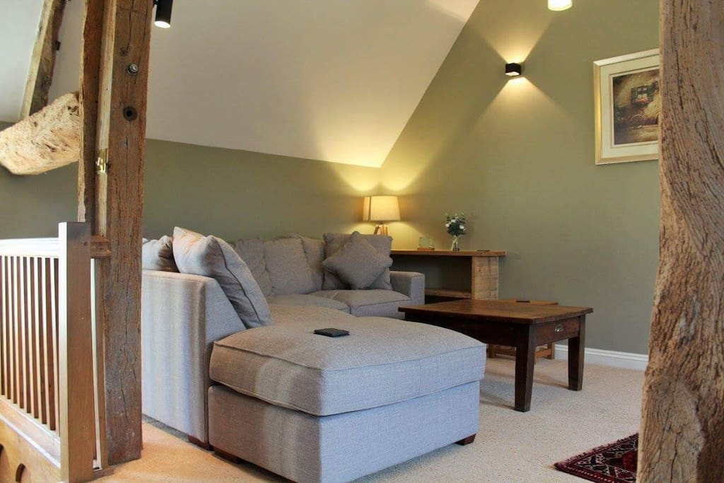 Upstairs sitting room with corner sofa, large TV with surround sound and blue ray DVD.