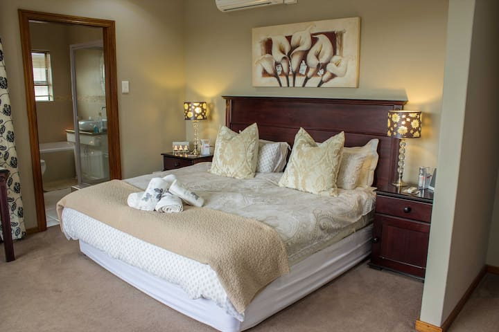 Main Bedroom with King size bed, AC, DSTV and Ensuite bathroom.