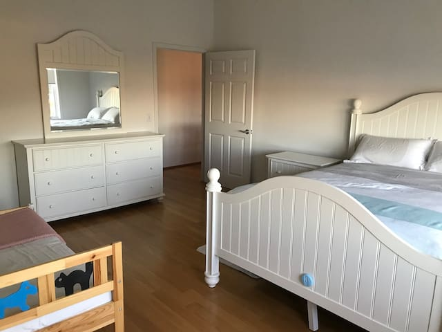 bedroom with queen size bed and toddler's bed
