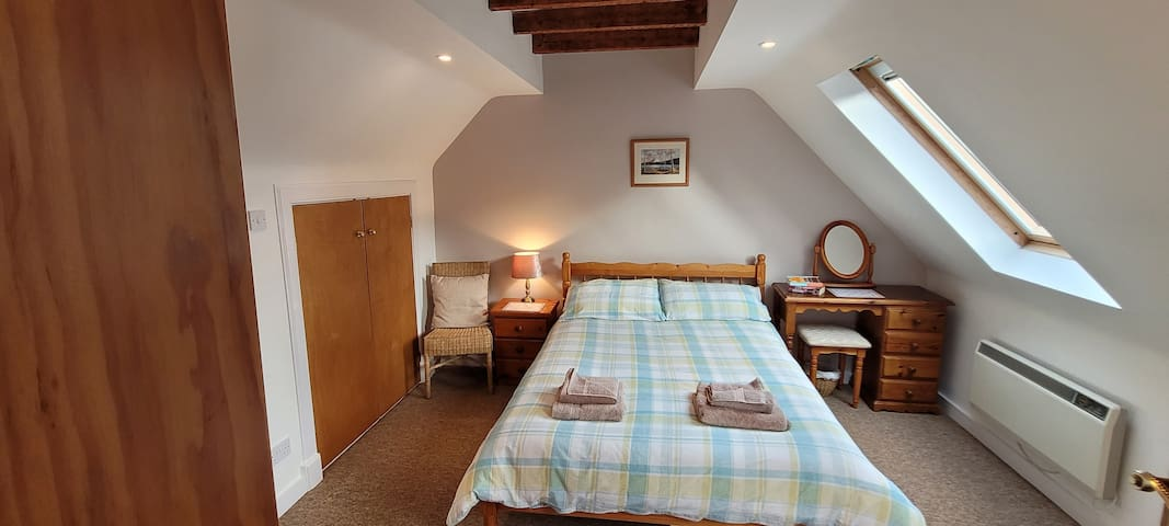 Bedroom 2 - double bed, 2 shallow steps down into room from landing, beamed ceiling, 2 velux windows, plenty of storage areas