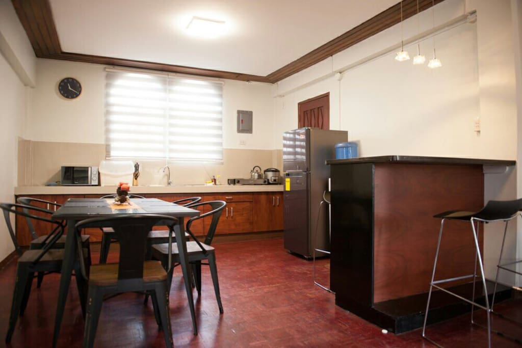 Dining area and kitchen with amenities (Fridge, hot and cold water dispenser, microwave, electric stove, and others)