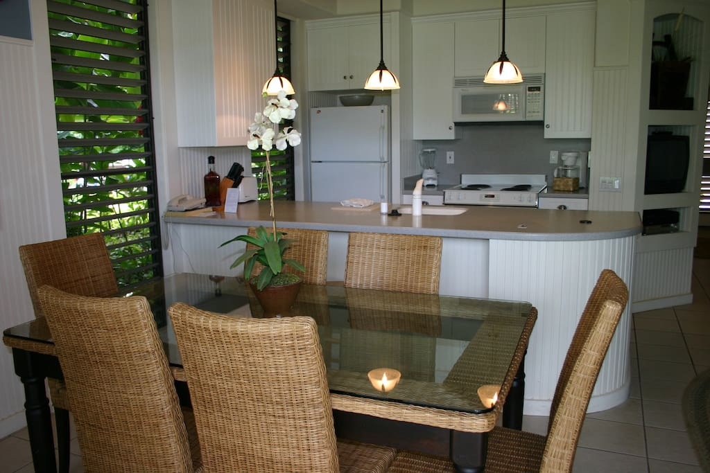 Dining room table and kitchen in our Kiahuna Beach House #52