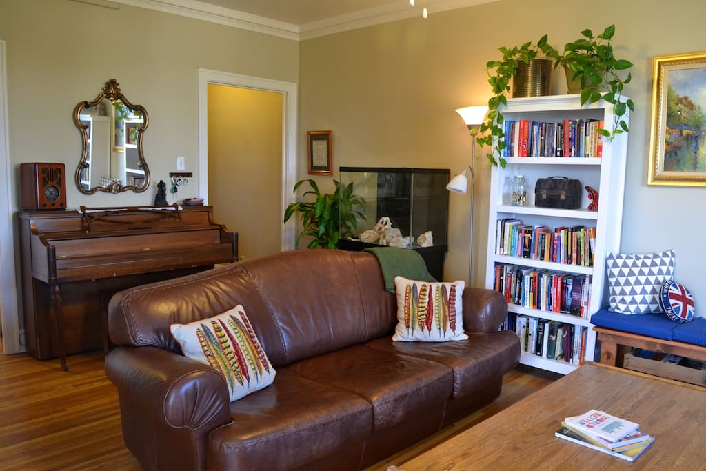 Bright, spacious living room, complete with piano. The leather couch is extremely comfortable for both lounging and napping on.