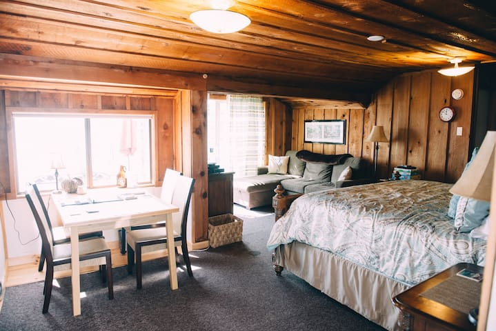 The cottage is one large room with a dining area, king bed, and entertainment area.