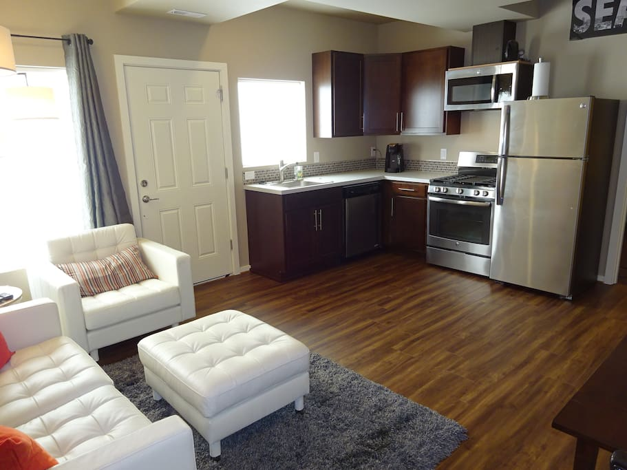 Modern conveniences of a gas cooktop, full size refrigerator and stainless steel appliances.