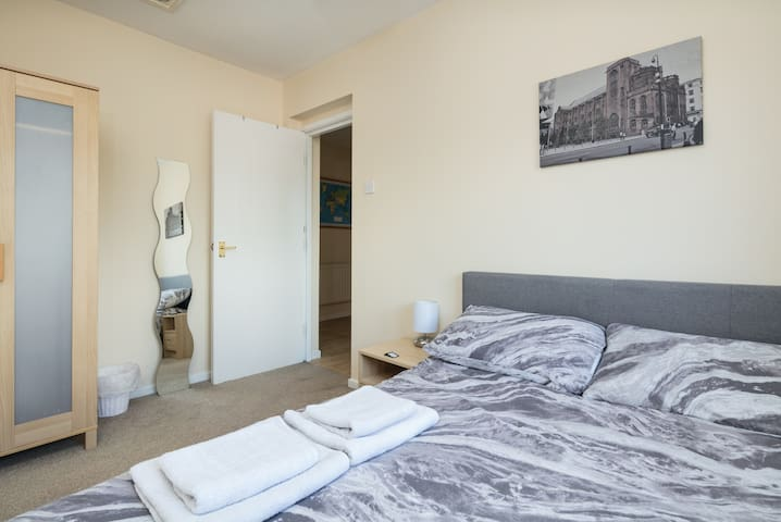 The room has a large wardrobe, a large mirror and a bedside table with lamp