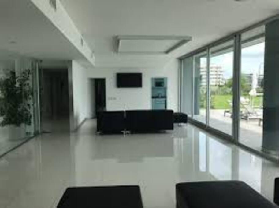 lobby con sofas, tv y cocina con heladera al lado de la pileta