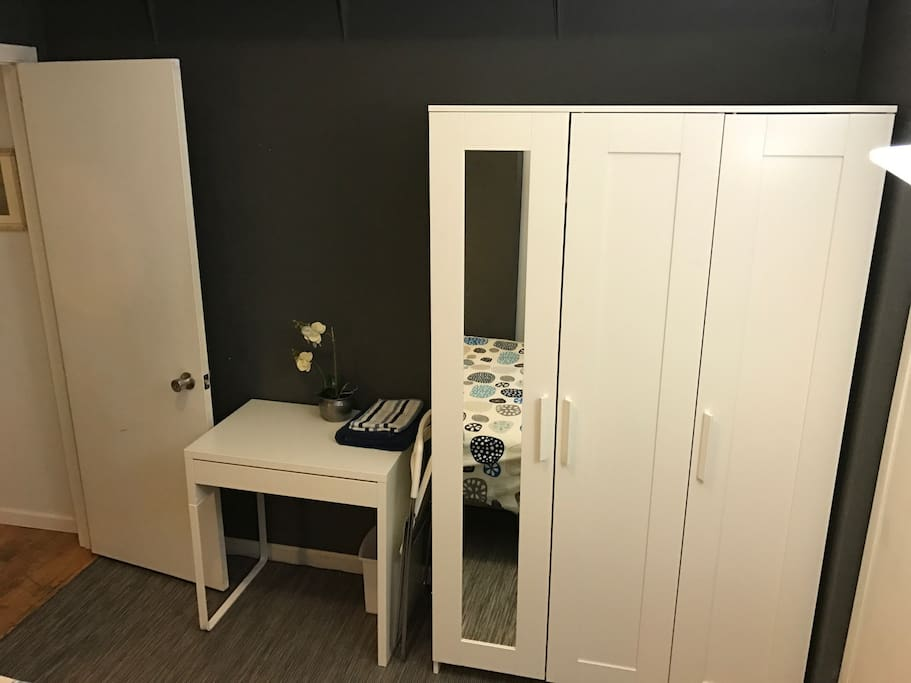 A small writing desk and a large closet for all your clothes.