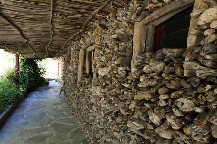 Driftwood piles along the walls outside the veranda.
