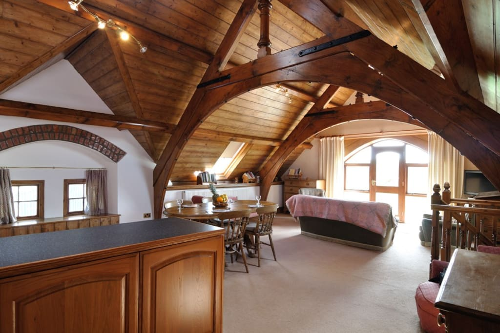 Open plan kitchen, dining, and living room all under a magnificent original beamed roof.