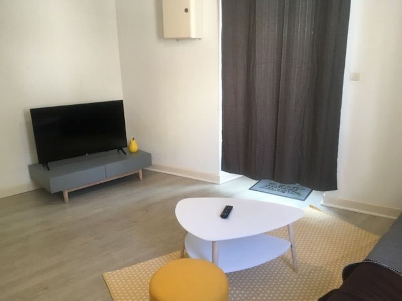 salon avec TV écran plat full HD canapé convertible confortable maison du monde.