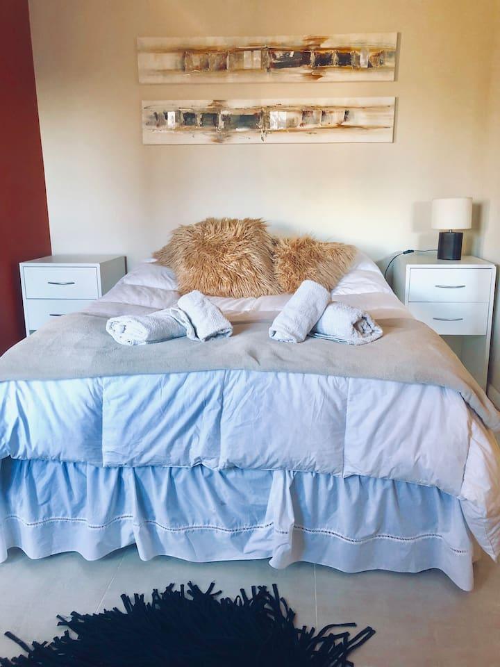 Contamos con una habitación con cama sommier matrimonial de dos plazas y media,  con mesas de luz, un butacón y un mueble chico para guardar la ropa durante la estadía.
