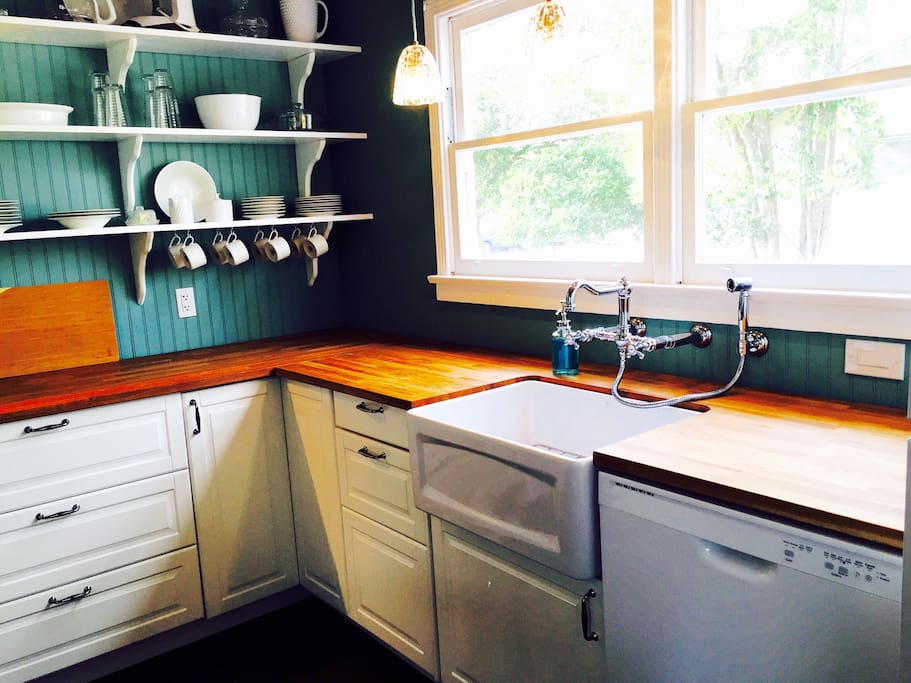 Farmhouse sink with wall mounted faucet and sprayer. Large kitchen window lets in lots of natural light.