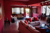 Living room with AC, 2 pairs of sofas, stools, and dinning table with 6 chairs.