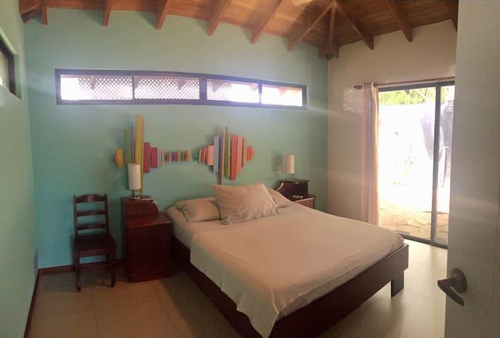 Bedroom. Queen bed, desk, nightstands, hangers, chair.