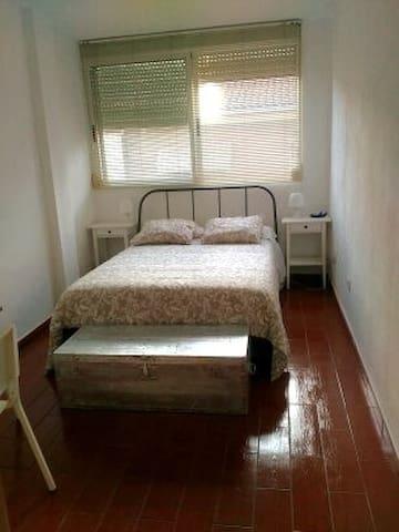 Habitación  de matrimonio con mesa para desayunar y un gran armario.