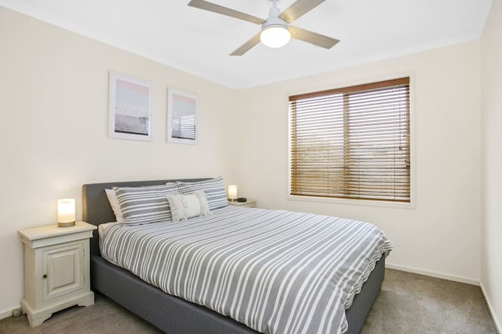 A 2nd Queen bedroom with ceiling fan is beautifully appointed with luxury hotel quality sheets and bath towels, making your stay as pleasurable as possible. A central bathroom with shower, bath, vanity and separate toilet is down the hall.