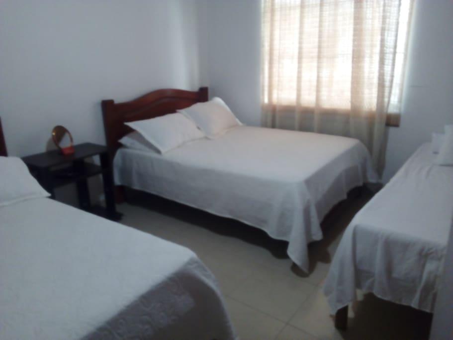habitacion con dos camas dobles y una sencilla, aire acondicionado tv y baño compartido