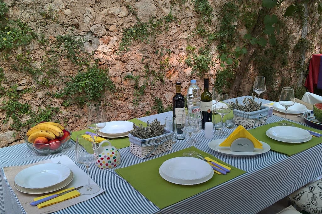 Dining table on the terrace in garden surrounded with stone wall