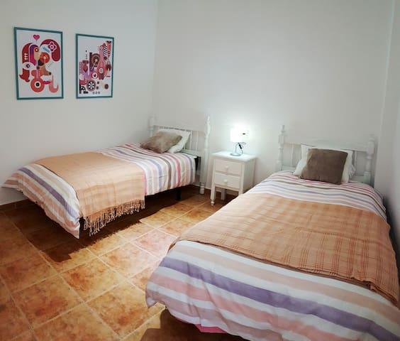 Dormitorio doble con camas de 90x190 cm, mesita de noche y lamparita.