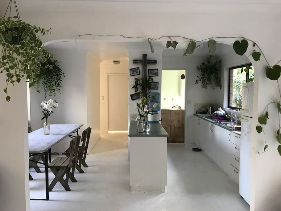 kitchen & dining area, a artist house it is what it is, white floors loads of plants. Basic kitchen wear. Y cook when the road house cafe is only footsteps away