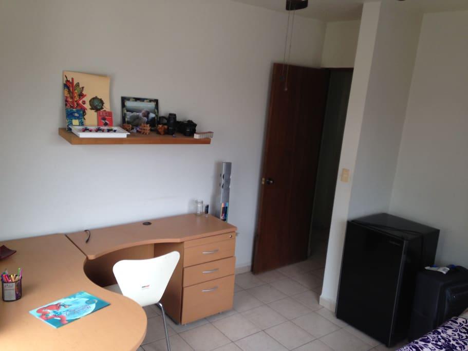 Cama individual, escritorio y frigobar.
