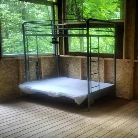 Screened in porch with bed frames for your air mattress or sleeping pad.