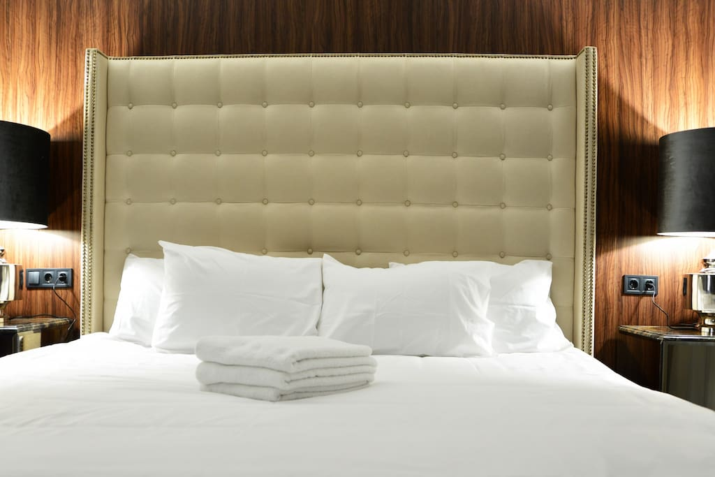 Elegant bedroom with large exceptionally comfortable bed with all cotton sheets and towels.