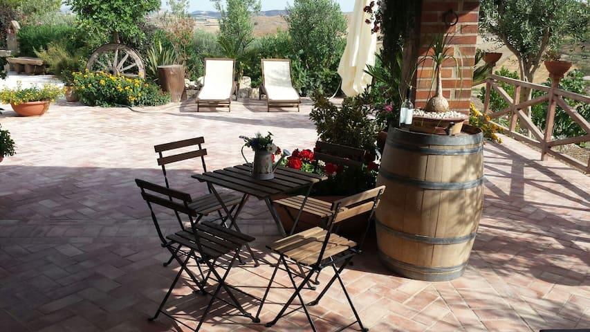 Veranda con tavolino da colazione, dondolo, sdraio e ombrellone per godersi il sole della Sicilia