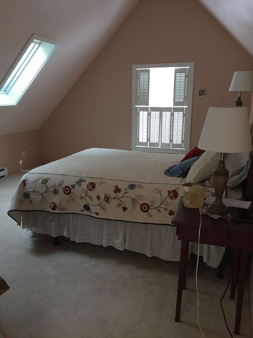 Upstairs spacious bedroom with queen bed and TV.