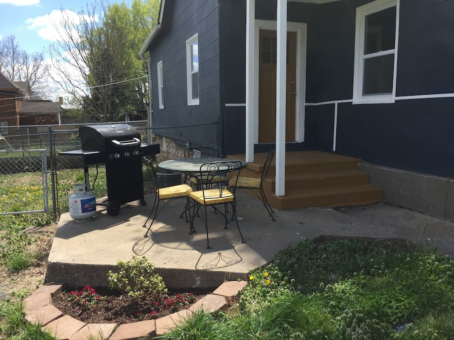 Side porch with gas grill and seating for four off kitchen.