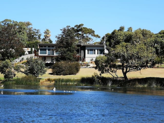 Looking towards your accommodation from the other side of the lake. Your unit is on the bottom level of the house.